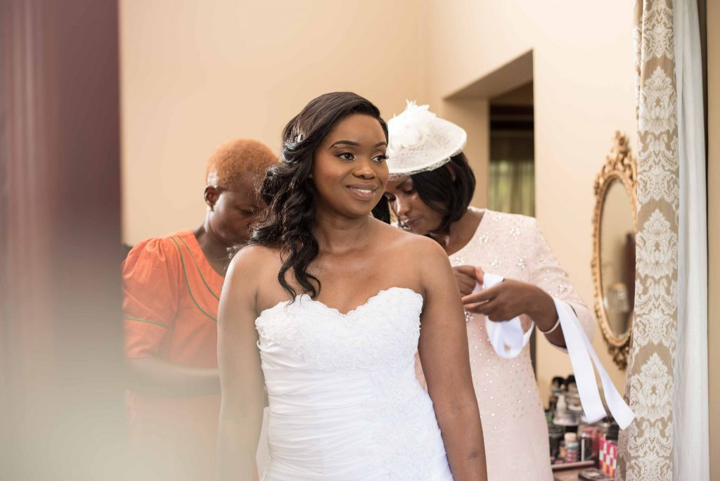 Bride dressing up before her wedding - kundai mendissa dube and ralph kangai wedding - Real Zimbabwe weddings photos - African Weddings on Wedding Expos Africa