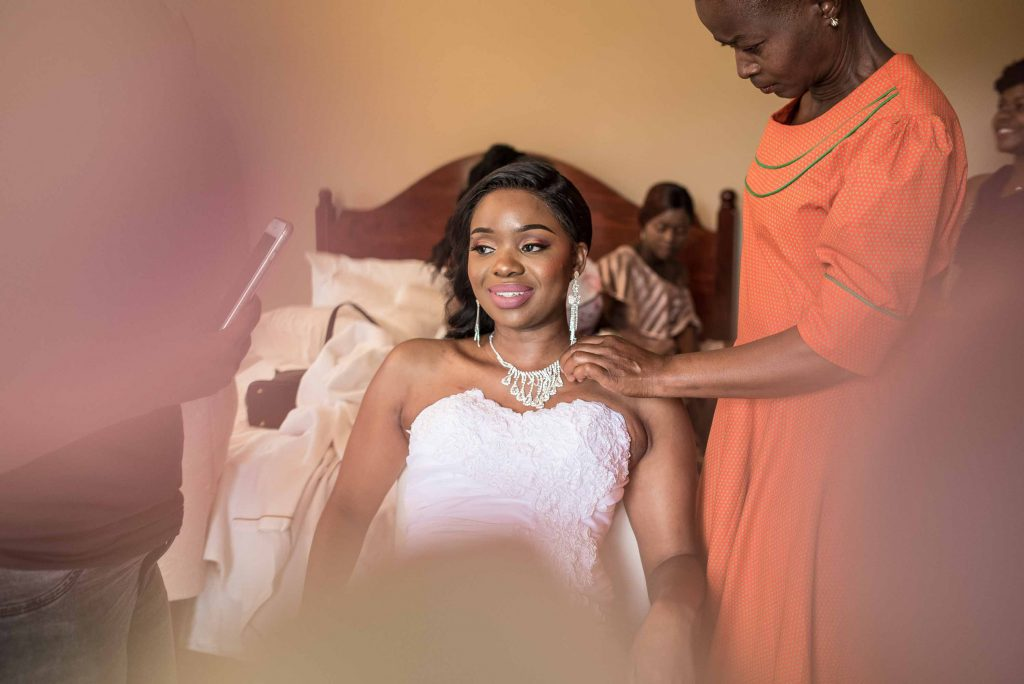 bride puts on her wedding jewellery - kundai mendissa dube and ralph kangai wedding - Real Zimbabwe weddings photos - African Weddings on Wedding Expos Africa